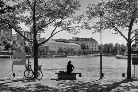 A lonely man is waiting for the ferry at the harbor or Helsinki, the capital of Finland on a summer day. He has left his bicycle in the shade of a small tree.