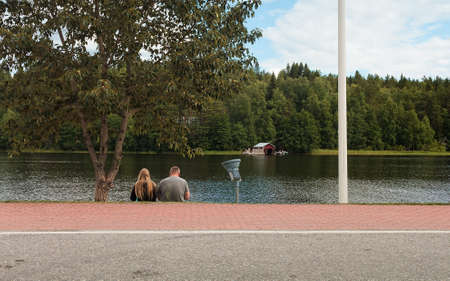 A couple is sitting on a pier by a lake and eating ice cream at Viitasaari, Finland. They are resting a bit by the waterfront before continuing their trip.