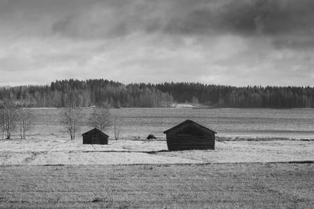 Two old barn houses stand on the autumn fields by a lake in the Northern Finland. The skies are quite cloudy and grey. The weather is turning bad quickly.