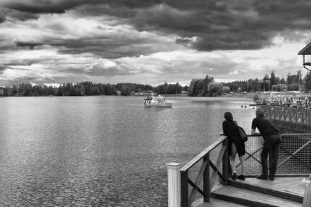 A couple is watching a boat arriving to the pier at Viitasaari, Finland. The place is a very popular place for people to have a rest while traveling. Stock Photo