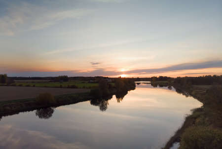 The autumn sun sets over the fields and river at the Northern Finland. The river water is very still on this calm evening.