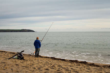 A lonely fisherman standing by his rod at a beach in Cornwall, England. The sun starts to set in the background.