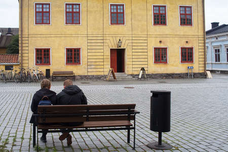 A young couple is sitting and relaxing at the market by the town hall of the historical old town of Rauma, Finland.