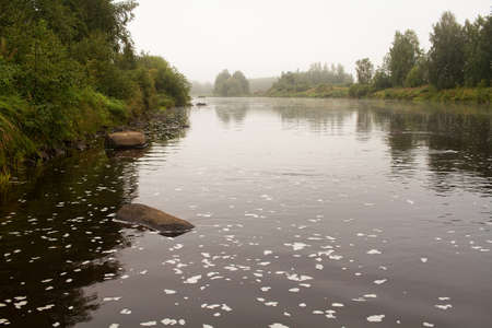 The autumn mornings are misty over the river at the Northern Finland. The river flows slowly by the rocks.