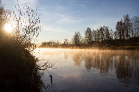 The autumn mornings are very misty at the Northern Finland. The sunrise colors the mist rising from the river beautifully. Stock Photo