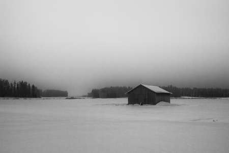 Early winter morning on the snowy fields at the Northern Finland. The mist rises over the snow covered barn houses.