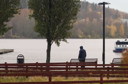 A lonely man is waiting something on a rainy day at the harbor of Jyväskylä, Finland.