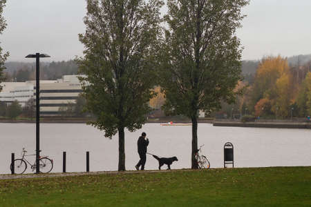 A man walks his dog on a rainy autumn day at the path surrounding a lake in Jyväskylä, Finland. Stock Photo