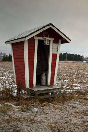 A milk shelter by the frosty fields on an early winter day. The snow has not fallen yet but everything is covered in frost.