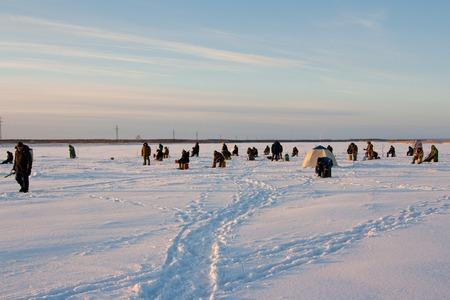 natural ice pastime: Fisherman enjoying a days fishing on the ice Stock Photo