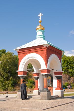 baptized: priest baptized in front of the chapel. Chapel of All Who Sorrow joy. Russia, Karelia Valaam Island. Stock Photo