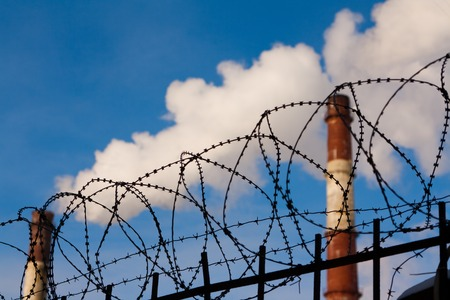 barbed wire and pipe enterprises on the background of blue sky. Russia Saint Petersburg Stock Photo