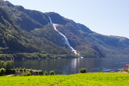 Summer mountain Langfossen waterfall on slope (Etne, Norway) in sunny day.