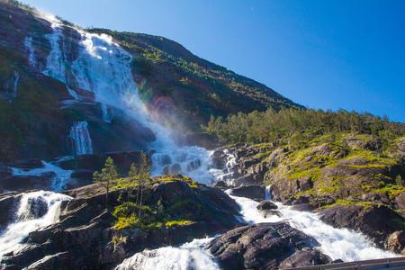 Summer mountain Langfossen waterfall on slope (Etne, Norway) in sunny day.