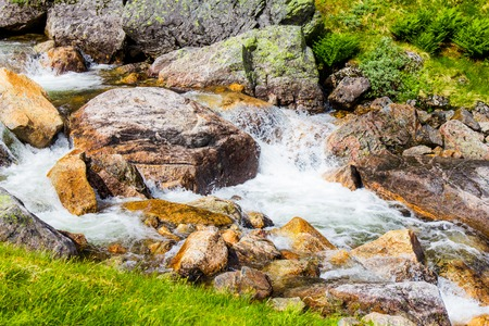Beautiful view on the mountain river near the road, against the woody mountains, originating from a thawing glacier. the beginning famous of waterfall Langfossen, Norway.