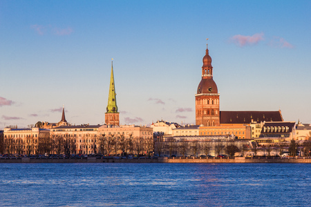 Riga, Latvia. The View Of 11 November Embankment Of River Daugava. The Towers, Steeples Of Riga Cathedral, St. Peters Church And St. Saviours Anglican Church In Old Town In Summer Under Blue Sky. Stock Photo