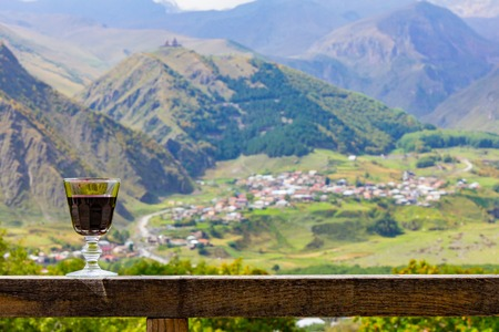 A glass of Georgian red Wine stands on a wooden railing on the background of the Georgian village and Kazbeg mountain. Near the village of Stepantsminda on the Georgian military road. Kazbegi Georgia