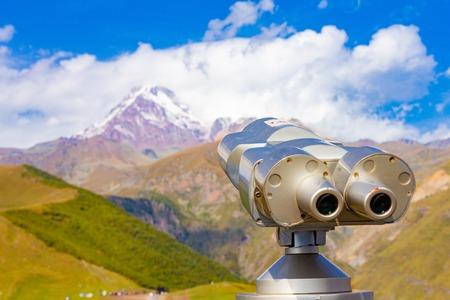Binoscope directed towards the snowy mountain tops of Kazbeg from the view point Gergeti Trinity Church Tsminda Sameba Holy Church near the village of Gergeti in Georgia