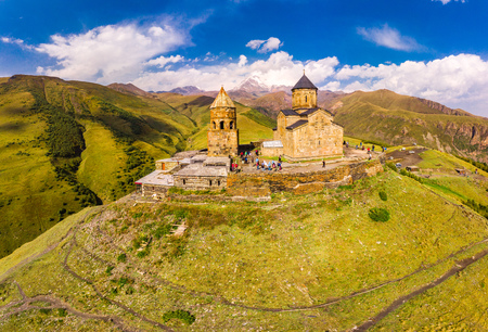 Beautiful Top view from drone to Tsminda Sameba or Holy Trinity Church Near Village Of Gergeti In Georgia and of the high mountain Kazbek, Caucasus mountains. Public place to visit.
