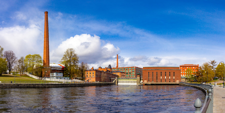 Beautifull panoramic view at Water dam of old Hydroelectric power station on Tammerkoski river and old traditional industrial buildings on a sunny summer day. Center of downtown Tampere, Finland.