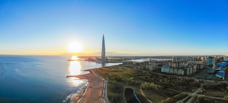 Saint Petersburg, RUSSIA - April 16 2019: Public, business complex Lakhta center, Skyscraper Gazprom headquarters. Gulf of Finland. Clear blue sky on sunset. Reflection in water. Top view aerial drone