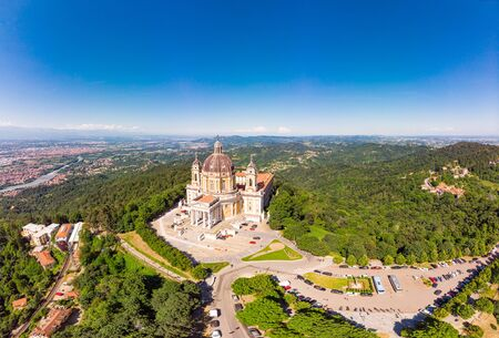 Beautifull aerial panoramic view to the famous from the drone Basilica of Superga in sunny summer day. The cathedral church located at the top of hill in italian Alps mountains. Turin, Piedmont, Italy