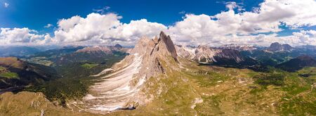 Amazing aerial top view on Seceda Mount peak and valley from drone. Trentino Alto Adige, Dolomites Alps, South Tyrol, Italy, Europe near Ortisei. Odle mountain range and Puez massif, Val Gardena. Stock Photo