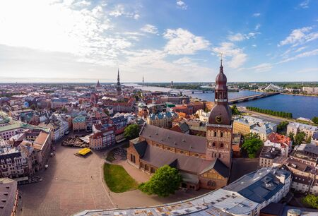 Beautifull aerial panoramic view from drone In sunny summer Day to histirical center Riga and quay of river Daugava. Famous Landmark - City Dome Cathedral church and Old Town Monument. Latvia, Europe.
