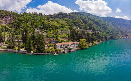 Beautifull aerial panoramic view from the drone to Varenna famous old Italy town on bank of Como lake. High top view to villa Monastero landscape, green hills, mountains and city in sunny summer day