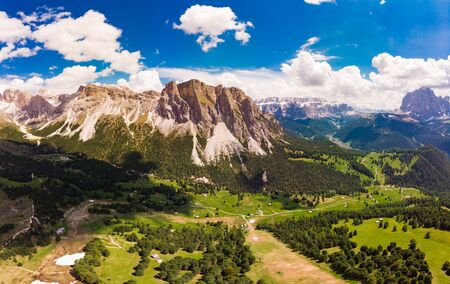 Aerial top view from drone to Col Raiser plateau In sunny summer Day. Scenery of rugged Sella Mountain with green valley on grassy hillside village St. Cristina di Val Gardena, Bolzano, Seceda Italy.