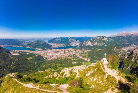 Beautiful panoramic sunrise landscape at town Lecco, lake Como in sunny summer day. Stunning airial view to cross on top of mountain from drone near viewpoint Piani Pizzo dErna, alps, italy, Europe
