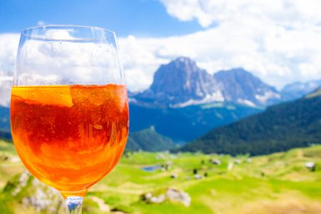 View of the traditional Italian alcoholic drink on the background of colorful Italian meadows and the Dolomites Alps mountains. village St. Cristina di Val Gardena Bolzano Seceda, Italy.