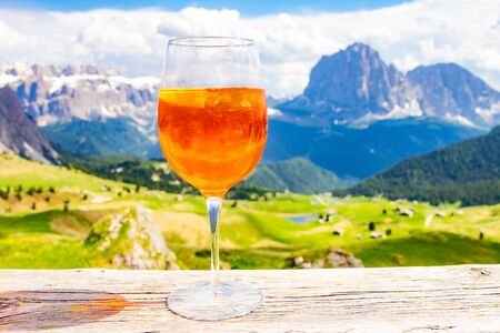 View of the traditional Italian alcoholic drink  on the background of colorful Italian meadows and the Dolomites Alps mountains. village St. Cristina di Val Gardena Bolzano Seceda, Italy. Stock Photo