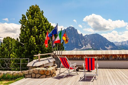Beautiful view to place of rest with sunbeds near funicular Col Raiser, captured with one of the dolomites famous mountains, the Sassolungo or Longkofel, in the background, on sunny summer clear day.