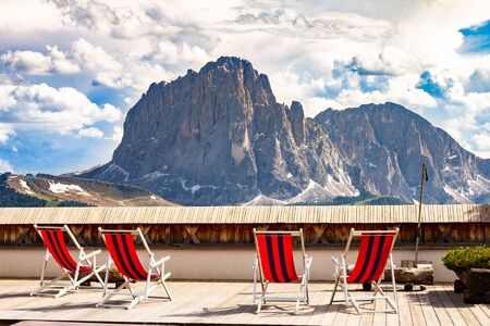 beautiful view to place of rest with sunbeds near funicular Col Raiser, captured with one of the dolomites famous mountains, the Sassolungo or Longkofel, in the background, on sunny summer clear day