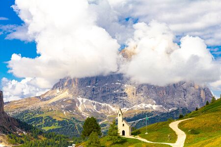 San Maurizio chapel on the passo di val Gardena with mountain view in background, between the Sella massif and Cirspitzen near Ortisei. Alps, Dolomites, Groeden, Bolzano, Trentino Alto Adige, Italy. Stock Photo