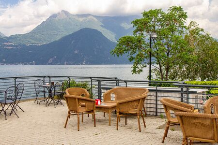 Beautiful view from terrace cafe of the overlooking the high mountains and shore lake Como. Empty wicker restaurant chairs are waiting for guests in a chic restaurant in the ancient city of Varenna. Stock Photo