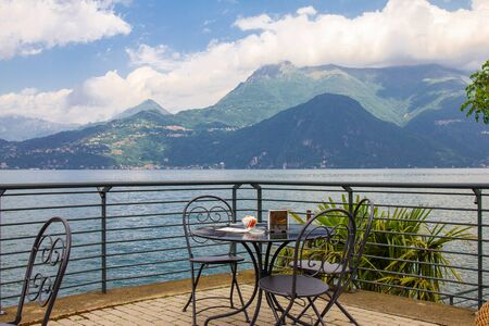 Beautiful view from terrace cafe of the overlooking the high mountains and shore lake Como. Empty wicker restaurant chairs are waiting for guests in a chic restaurant in the ancient city of Varenna
