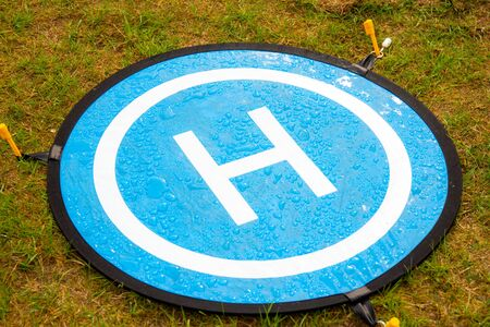 Blue landing place for drone with drops of water. The Landing Parking Pad take off platform for copter is used in high lawn and dusty ground in order to deface the spoilage of a high priced aircraft. Stock Photo