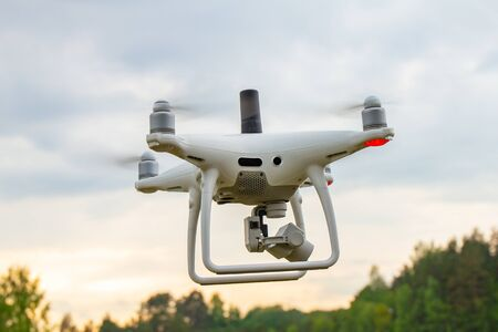 UAV White drone Quadr copter in flight with geodesic module and digital camera explores the area on the background of a sunset with clouds. The copter in the air take aerial photo in the blue sky.