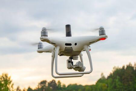 UAV White drone Quadr helikopter w locie z modułem geodezyjnym i kamerą cyfrową eksploruje teren na tle zachodzącego słońca z chmurami. Śmigłowiec w powietrzu robi zdjęcie lotnicze na błękitnym niebie.