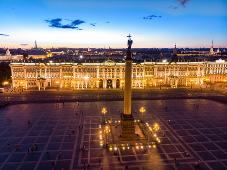 Aerial front view at the Winter Palace building in white nights, exterior Palace Square and Aleksandr Column at summer. Top view from drone. Saint-Petersburg, Russia