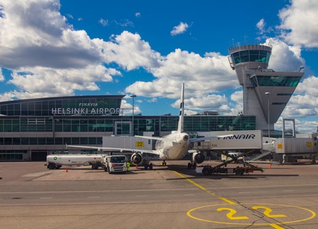 Helsinki Airport Finland 26.07.2019: Finnair airline technicians men load luggage from container into the compartment in the tail of the aircraft. Two Airbus standing on the runway and waiting flight.