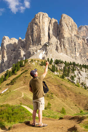 European man takes off a drone in the Alpain Dolomites in Passo Gardena. Copter pilot wants to make beautiful panoramic images and video of the mountain range Selva di Val Gardena. South Tirol, Italy.