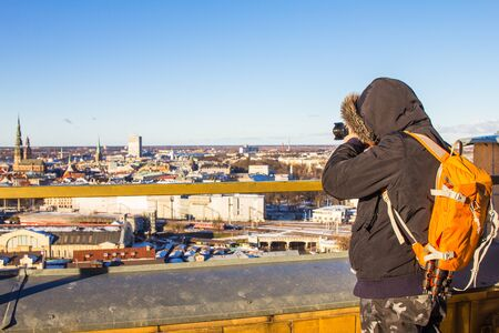 Photographer with big bag taking picture landmark the ancient european city from a high view point. Latvian Academy of Sciences. Sunny winter day. Riga, Europe, Baltic, Latvia. Travel photos concept.