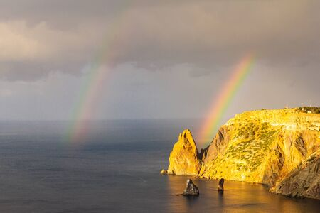 Scenic view from Jasper beach near St. George Monastery to Cape Fiolent in rainy day with rainbow. Rocky coast black sea and cliff, Sevastopol, Crimea, Russia. Landscape Mountains surround the bay. Stockfoto - 133101078