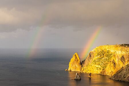 Scenic view from Jasper beach near St. George Monastery to Cape Fiolent in rainy day with rainbow. Rocky coast black sea and cliff, Sevastopol, Crimea, Russia. Landscape Mountains surround the bay.
