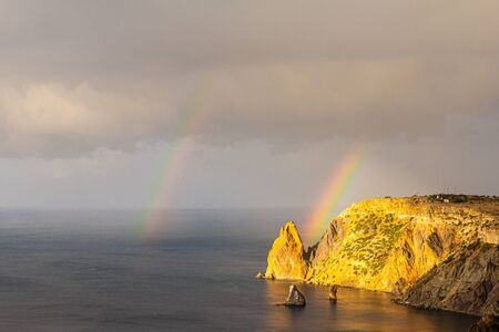 Scenic view from Jasper beach near St. George Monastery to Cape Fiolent in rainy day with rainbow. Rocky coast black sea and cliff, Sevastopol, Crimea, Russia. Landscape Mountains surround the bay. Stockfoto - 133101147