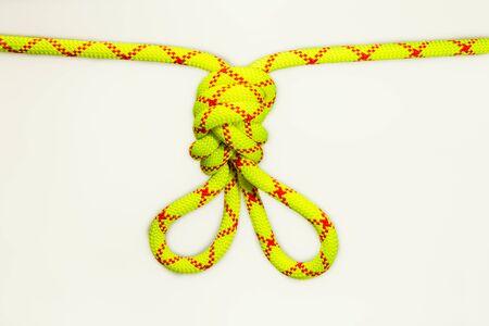 Doppelte Acht 8 Knoten oder flämische Schlaufe oder Hasenohren zum Klettern oder Ausgleichen von Ankern im Alpinismus. Gespanntes farbiges, grünes Seil für die persönliche Sicherung. Isoliert auf weißem Hintergrund