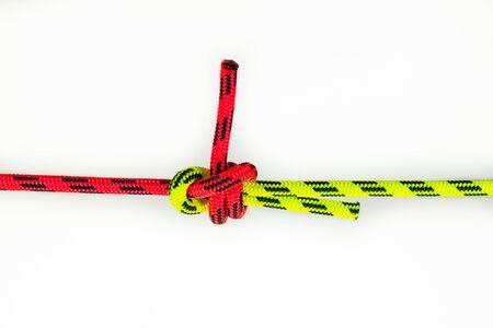 Double Sheet, Bucket Bend oder Weber's Hitch Bindung von zwei farbigen roten und grünen Seilen Knoten zum Verbinden von Leitungen mit unterschiedlichem Durchmesser oder Steifigkeit Isoliert auf weißem Hintergrund. Standard-Bild